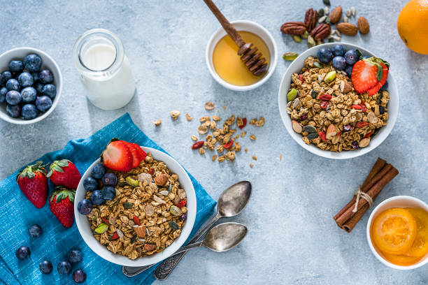 Healthy granola breakfast: two bowls filled with breakfast cereal, dried nuts, seeds and fruits like blueberries and strawberries shot from above on bluish tint table. A milk jar and a honey container are at the right and some fruits and nuts are all around the bowls. XXXL 42Mp studio photo taken with Sony A7rii and Sony FE 90mm f2.8 macro G OSS lens