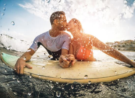 Happy sportive couple kissing while surfing in the ocean - Surfers holding hands on surfboard having a tender moment - Sport, extreme, relationship love and healthy lifestyle concept